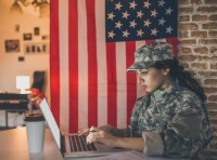 Young female soldier working on a laptop with United States flag in the background