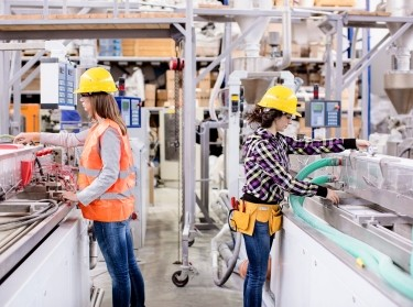 Two young women working in a factory