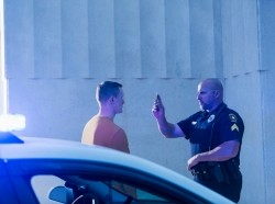 Police officer giving sobriety test to young man, with a police cruiser in the foreground