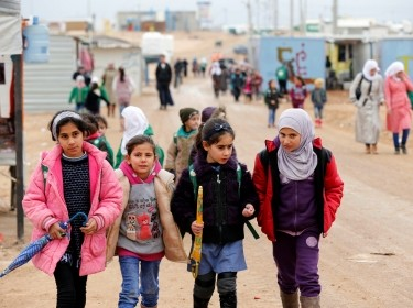 Syrian refugee children walk to the school during rainy weather at the Al Zaatari refugee camp in Mafraq, Jordan, December 18, 2016