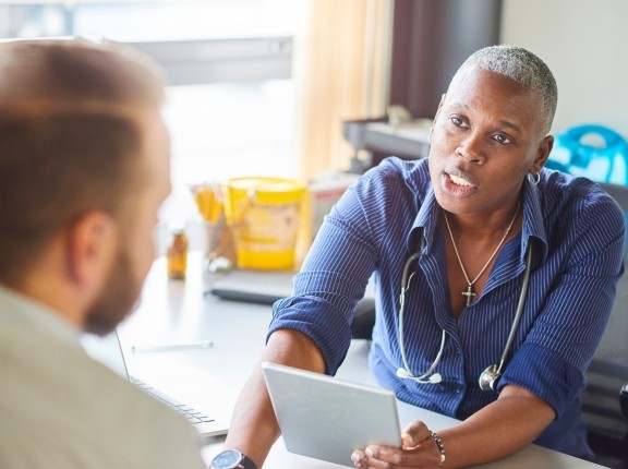 A doctor sits at her desk and talks with a patient