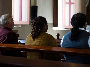 View from the back of a church, focusing on the backs of three people sitting on a wooden pew