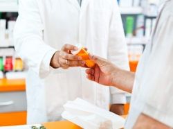 Pharmacist handing a pill bottle to a male customer
