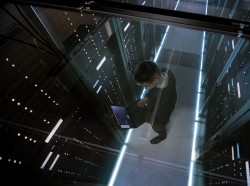 Top view through the glass of IT engineer working with laptop in data center full of active rack servers, photo by Gorodenkoff/Adobe Stock