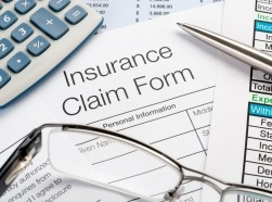 Close up of insurance claim form with pen, calculator, and eyeglasses