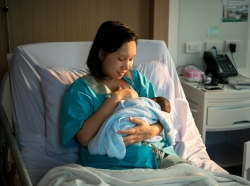 Mother in hospital bed breastfeeding her newborn baby