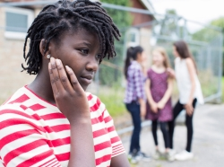 African American girl in foreground, ignored by a group of girls in the background