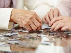 An elderly person's hands and a young person's hands working on a jigsaw puzzle