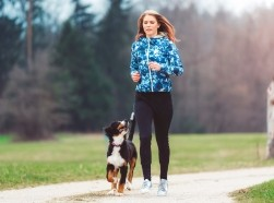 A woman running in a park with a dog