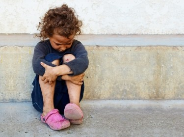 Poor, sad girl sitting against concrete wall