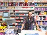 Convenience store check out, with clerk standing near the cash register