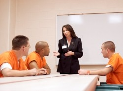 Three male inmates wearing orange prison jumpsuits sit at a table while a woman in a suit speaks.