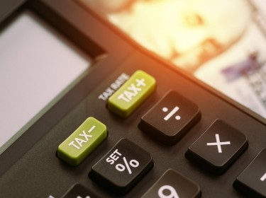 Close up of calculator buttons for tax increase or tax decrease with blurred American dollars in the background