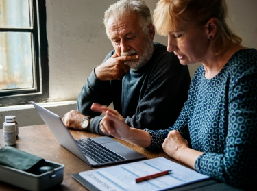 Woman and elderly man looking at a laptop with insurance forms on the table nearby