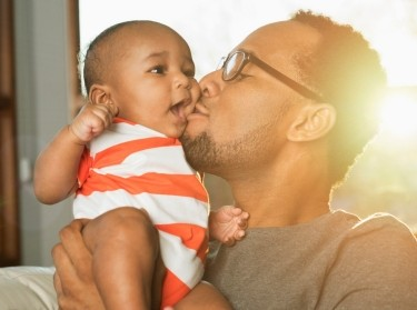 Father kisses baby son on cheek