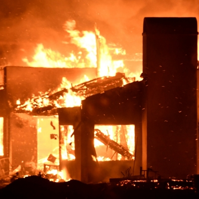 A house burns as firefighters battle a fast-moving wildfire that destroyed homes driven by strong wind and high temperatures forcing thousands of residents to evacuate in Goleta, California, July 7, 2018