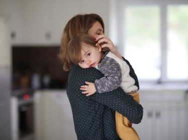 Mother cuddling toddler son in kitchen