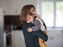Mother cuddling toddler son in kitchen