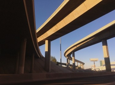 Freeway ramps viewed from underneath, against a blue sky.