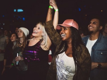 Group of women dancing at a concert, photo by Hero Images/Getty Images