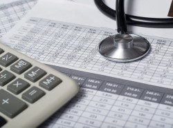 Calculator and stethoscope on financial statement, photo by seksan mongkhonkhamsao/Getty Images