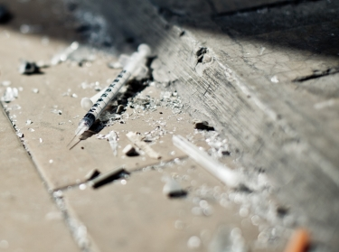 Used needle among debris on the ground, photo by sanjeri/Getty Images