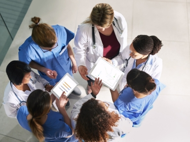 Group of medical practitioners in a circle, talking, seen from above, photo by Cecilie_Arcurs/Getty Images