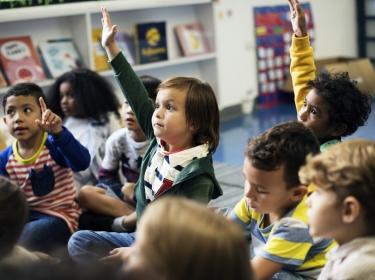 Children seated on floor of elementary school classroom, photo by Rawpixel.com/Adobe Stock