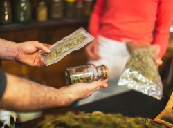 Close up of a man holding cannabis products in a cannabis dispensary, photo by CasarsaGuru/Getty Images