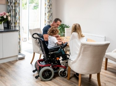 Boy with muscular dystrophy sitting at dining table with mother and father, playing a game, photo by JohnnyGrieg/Getty Images