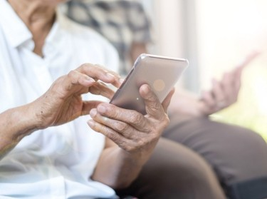Elderly couple holding smartphones, photo by Pornpak Khunatorn/Getty Images