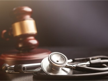 Stethoscope in the foreground, gavel in the background, photo by artisteer/Getty Images