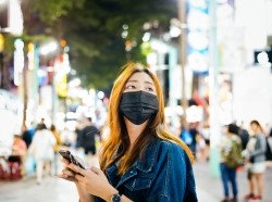 Woman wearing a mask and holding a phone, looking off into the distance, photo by izusek/Getty Images