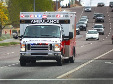 Ambulance with lights on driving down the highway, photo by ARHIT/Adobe Stock