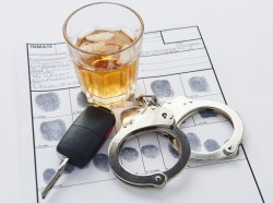 Glass of alcohol, keys, and handcuffs on top of an arrest record with fingerprints, photo by TheCrimsonRibbon/Getty Images