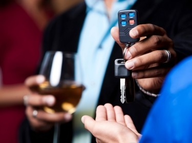 Close-up of a man holding a drink with one hand and giving his keys to another person, photo by avid_creative/Getty Images