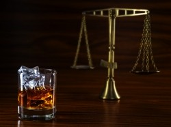 Glass of whiskey with scales of justice in the background