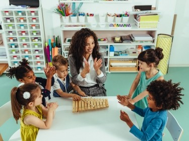 Preschool children and teacher playing with xylophone, photo by Bernard Bodo/Adobe Stock