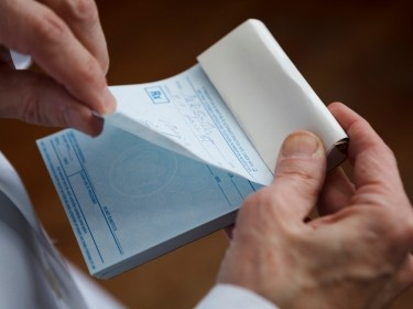Closeup of a doctor tearing a prescription off a pad, photo by wdstock/Getty Images