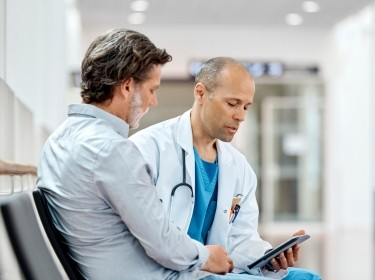 Doctor looking at a digital tablet and counseling a patient in a health care setting, photo by Morsa Images/Getty Images