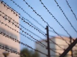 Barbed wire fence surrounding a prison. Photo by fortton / Getty Images
