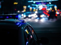 A police vehicle on a street at night with streetlights in the background. Photo by z1b / Getty Images