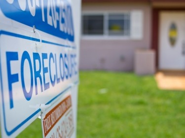 A foreclosure sign outside a house. Photo by Reicaden / Getty Images