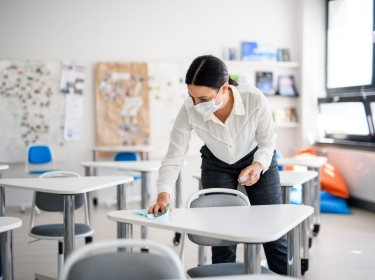 Teacher back at school after COVID-19 lockdown, disinfecting desks, photo by Halfpoint/AdobeStock