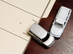 "Two toy vehicles in a collision on top of a manilla folder marked ""Plaintiff v Defendant"""