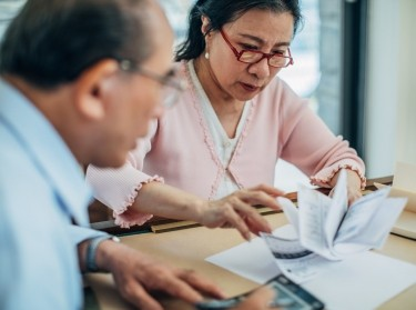 An elderly couple sit at a table reviewing financial documents. Photo by South_agency / Getty Images