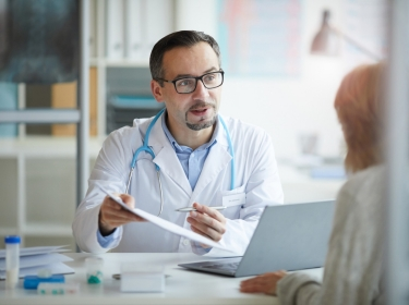 Doctor holding a clipboard and talking to a female patient, photo by AnnaStills/Getty Images