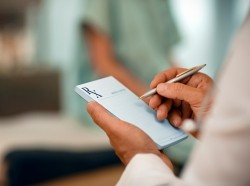 Close up of a doctor filling out a prescription, photo by stevecoleimages/Getty Images