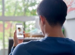 Close up of a young man from behind talking to a doctor on his smartphone, photo by Chainarong Prasertthai/Getty Images