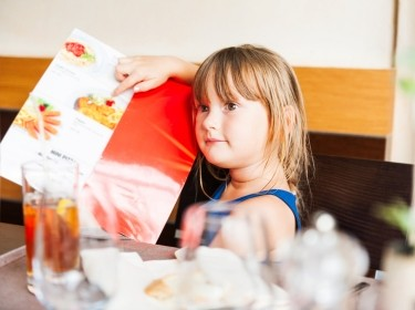 Girl pointing to her meal choice on a restaurant menu